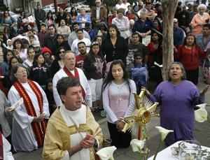 Fr. John Moneypenny, Fr. Brad Karelius and the Rev. Carolyn Estrada kneel before Blessed Sacrament
